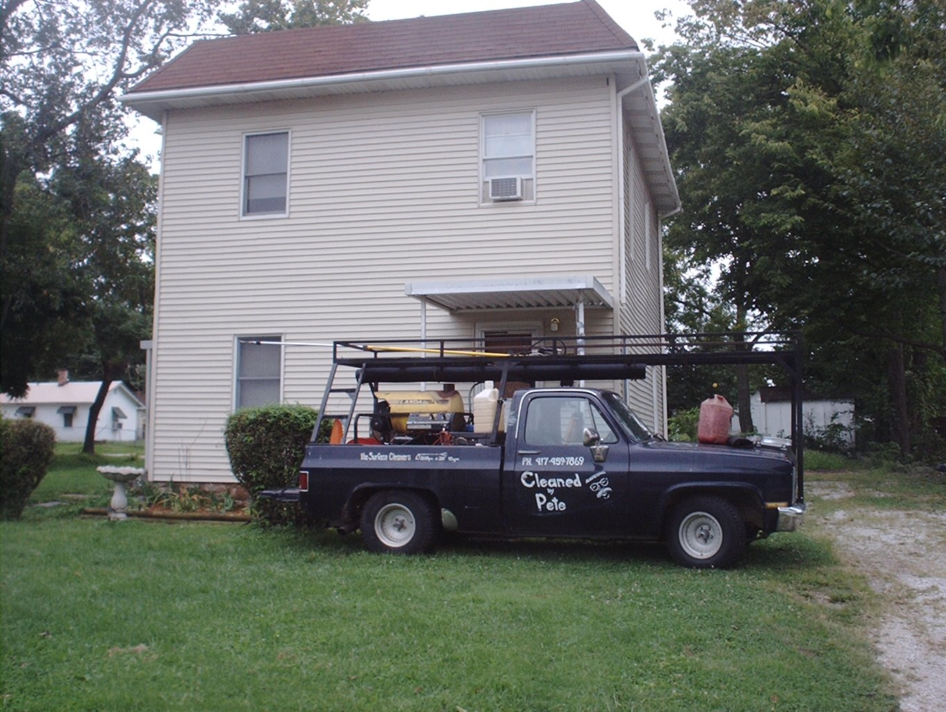 Service truck in front of completed two story house cleaning.